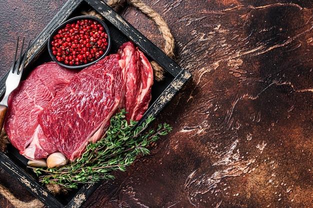 Surowy stek wołowy rib eye na drewnianej tacy z ziołami. ciemne tło. widok z góry. skopiuj miejsce.