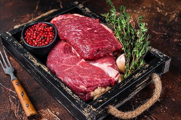 Surowy stek wołowy rib eye na drewnianej tacy z ziołami. ciemne tło. widok z góry.