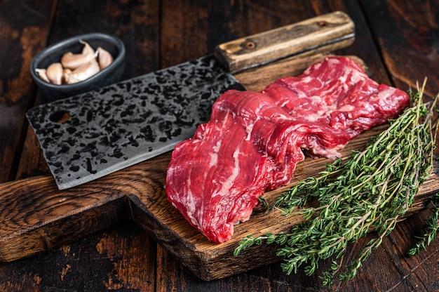 Surowy stek wołowy w spódnicy maczety na desce rzeźniczej z tasakiem