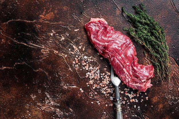 Surowy stek wołowy w spódnicy maczety na widelcu mięsnym