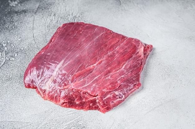 Surowy stek wołowy z boku lub z klapą. białe tło. widok z góry.