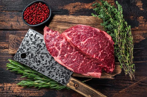 Surowy stek wołowy z czarnego angusa na desce mięsnej z tasakiem do mięsa