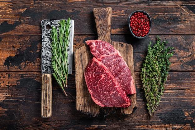 Surowy stek wołowy z czarnego angusa z denveru na desce rzeźnika z tasakiem do mięsa. ciemne tło drewniane. widok z góry.