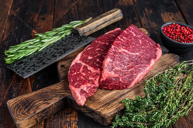 Surowy stek wołowy z czarnego angusa z denveru na desce rzeźnika z tasakiem do mięsa.