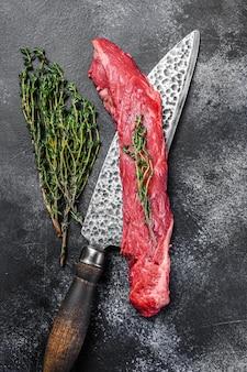 Surowy stek wołowy z maczetą na tasak do mięsa. czarne tło. widok z góry.