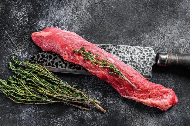 Surowy stek wołowy z maczetą na tasak do mięsa