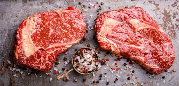 Surowy stek wołowy z mięsa marmurowego. przyprawy