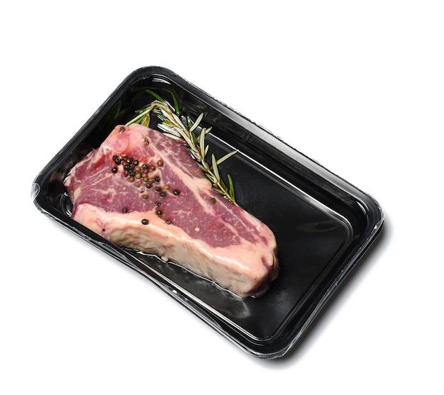 Surowy stek wołowy z nowego jorku jest zapakowany w plastikowy pojemnik i szczelnie zamknięty próżniowo. długotrwałe przechowywanie mięsa z rostbefu