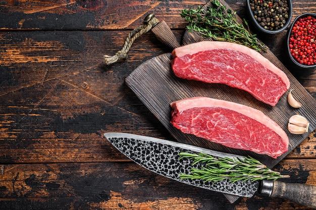 Surowy stek wołowy z polędwicy wołowej na desce do krojenia. ciemne drewniane tło. widok z góry. skopiuj miejsce.