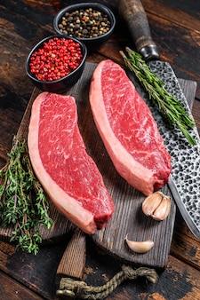 Surowy stek wołowy z polędwicy wołowej na desce do krojenia. ciemne drewniane tło. widok z góry.