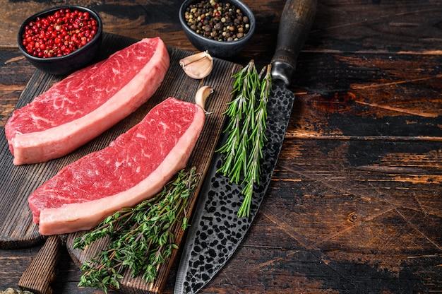 Surowy stek wołowy z polędwicy wołowej na desce do krojenia na drewnianym stole. widok z góry.