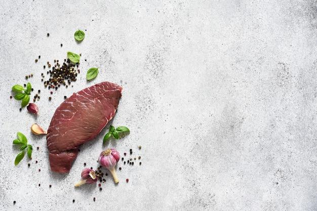 Surowy stek wołowy z przyprawami na betonowym tle, widok z góry. reklama.