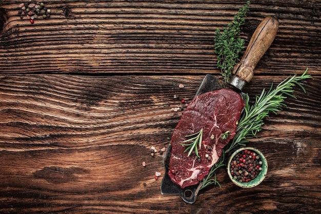 Surowy stek wołowy z rozmarynem pieprzowym na stary tasak do mięsa na ciemnym tle drewnianych. baner, miejsce przepis menu na tekst, widok z góry.