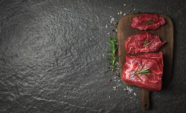 Surowy stek wołowy z rozmarynem zioła i przyprawy / świeże mięso wołowe w plasterkach na tle drewnianą deską do krojenia