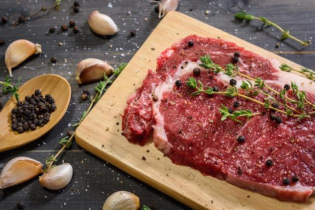 Surowy stek wołowy z ziołami i czosnkiem na drewnianej desce do krojenia na ciemnym tle drewna