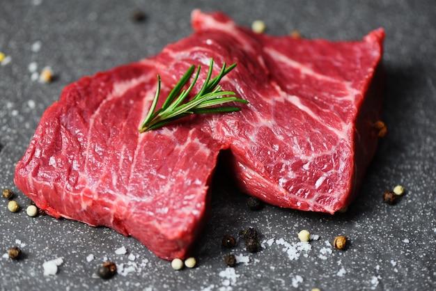 Surowy stek wołowy z ziołami i przyprawami - świeża wołowina krojona na czarnej powierzchni