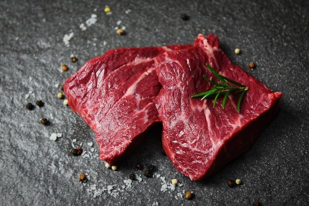 Surowy stek wołowy z ziołami i przyprawami. wołowina świeżego mięsa pokrojona na czarno