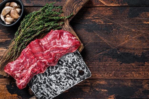 Surowy stek wołowy ze spódnicą maczety na desce rzeźnika z tasakiem. ciemne tło drewniane. widok z góry. skopiuj miejsce.