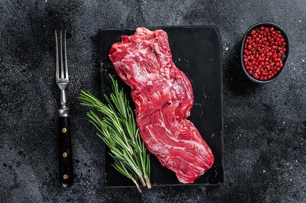 Surowy stek wołowy ze spódnicą maczety na marmurowej desce. czarne tło. widok z góry.