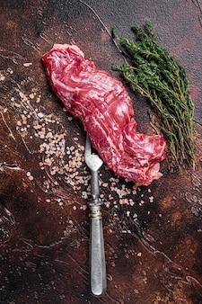 Surowy stek wołowy ze spódnicą maczety na widelcu do mięsa. ciemne tło. widok z góry.