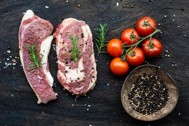 Surowy stek wołowy żeberka z rozmarynem pieprz pomidory i zioła.