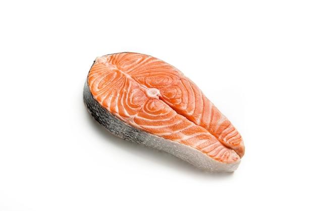 Surowy stek z czerwonej ryby na białym tle na białej ścianie. zbliżenie stek z łososia.