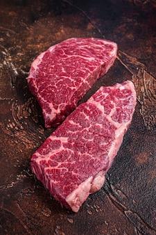 Surowy stek z denver marmurowe mięso wołowe. ciemne tło. widok z góry.