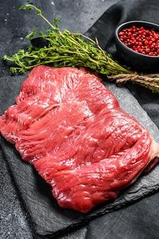 Surowy stek z flanki, marmurkowe mięso. widok z góry. skopiuj miejsce