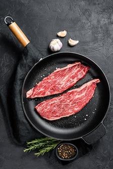Surowy stek z flanki na patelni. marmurowa wołowina czarna angus. czarne tło. widok z góry. miejsce na tekst