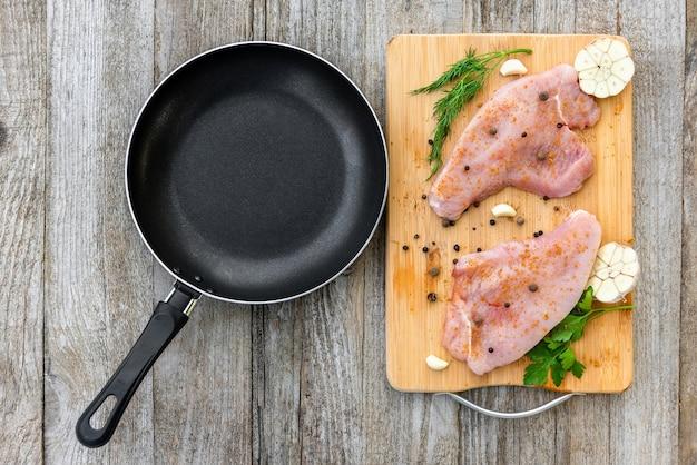 Surowy stek z indyka jest na desce do krojenia z przyprawami na drewnianym stole