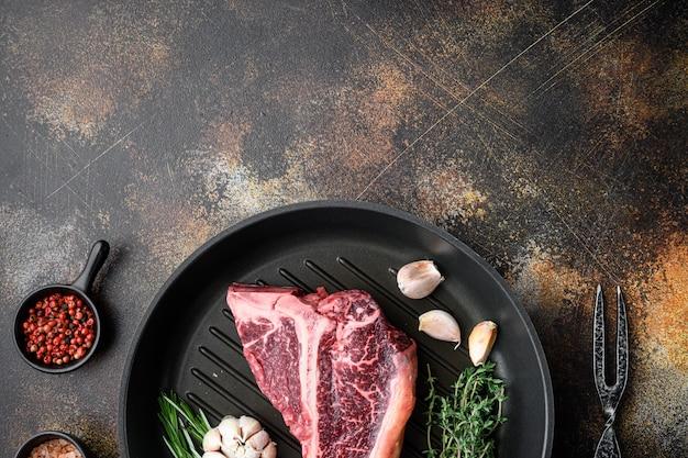 Surowy stek z kością z ustawionymi składnikami, na patelni żeliwnej, na starym ciemnym rustykalnym stole, widok z góry na płasko