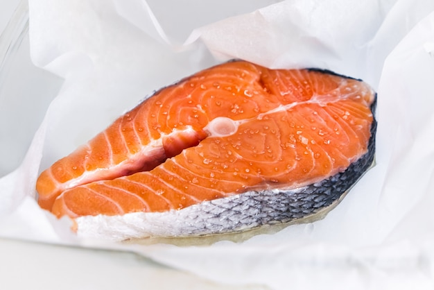 Surowy stek z łososia jest posypany różową solą himalajską. gotowanie stek z czerwonej ryby. owoce morza