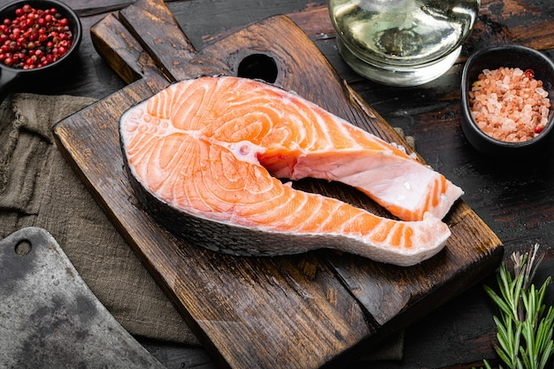 Surowy stek z łososia lub pstrąga i warzyw, na starym ciemnym tle drewnianego stołu