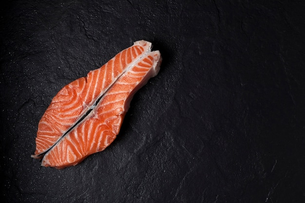 Surowy stek z łososia na czarnym tle z teksturą