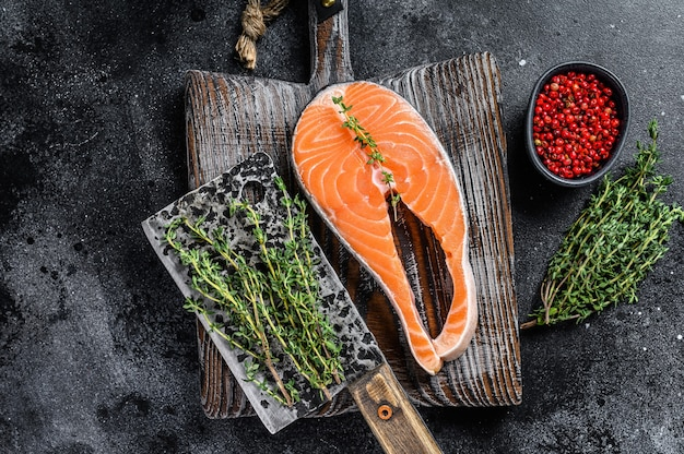 Surowy stek z łososia na drewnianej desce do krojenia rustykalne. czarne tło. widok z góry.