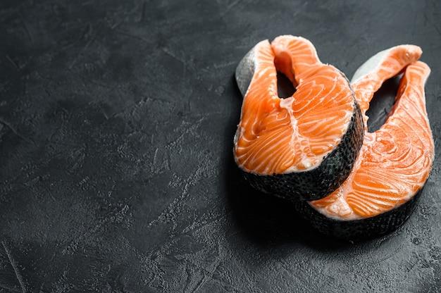 Surowy stek z łososia. ryba atlantycka. czarne tło. widok z góry. miejsce na tekst