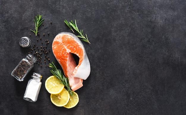Surowy stek z łososia, sól i rozmaryn na betonowym czarnym tle. składniki do gotowania ryb.