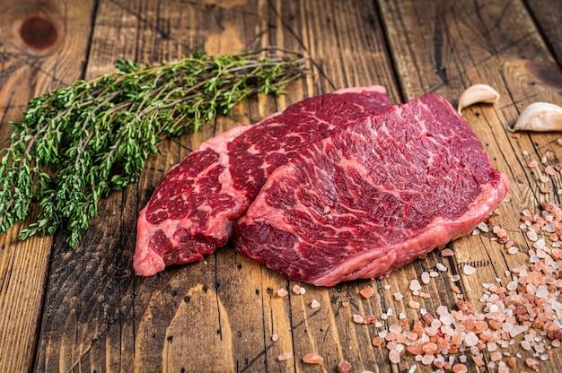 Surowy stek z mięsa denver lub top blade na stole rzeźniczym z ziołami. drewniane tła. widok z góry.