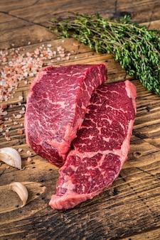 Surowy stek z mięsa denver lub top blade na stole rzeźniczym z ziołami. drewniane tło