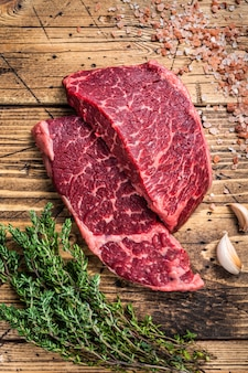 Surowy stek z mięsa denver lub top blade na stole rzeźniczym z ziołami.