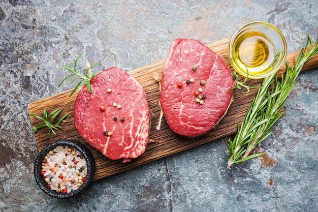 Surowy stek z mięsa marmurkowaty filet mignon z przyprawami na tle kamienia, widok z góry.