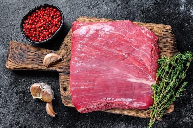 Surowy stek z mięsa wołowego flanki lub klapy na drewnianej desce do krojenia. czarne tło. widok z góry.