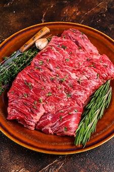 Surowy stek z mięsa wołowego spódnicy na rustykalnej płycie z ziołami. ciemne tło. widok z góry.