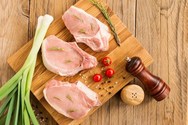 Surowy stek z młodej wieprzowiny na desce kuchennej i drewnianym stole z zieleniną cebulową, rozmarynem, pomidorami.