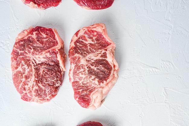 Surowy stek z najwyższej półki. wołowina ekologiczna. białe tło z teksturą. widok z góry z miejscem na tekst.