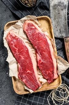 Surowy stek z polędwicy na drewnianej tacy z tasakiem. marmurowa wołowina widok z góry.