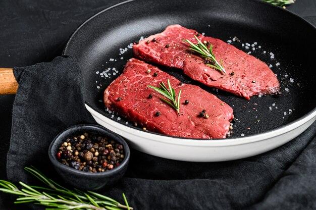 Surowy stek z polędwicy na patelni. mięso wołowe. czarne tło. widok z góry