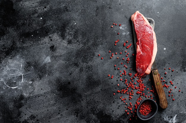 Surowy stek z polędwicy na tasaku. marmurowa wołowina widok z góry