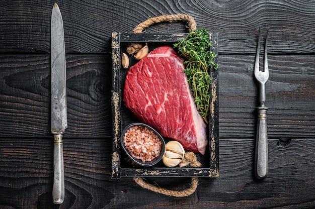 Surowy stek z polędwicy wołowej lub pikanha w drewnianej tacy z ziołami