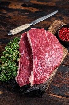 Surowy stek z polędwicy wołowej lub stek picanha na desce z tymiankiem. ciemne drewniane tło. widok z góry.